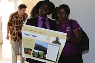4th Equal Prize Winners, Mr. and Mrs. Takura; Trustee John Wilson in the background